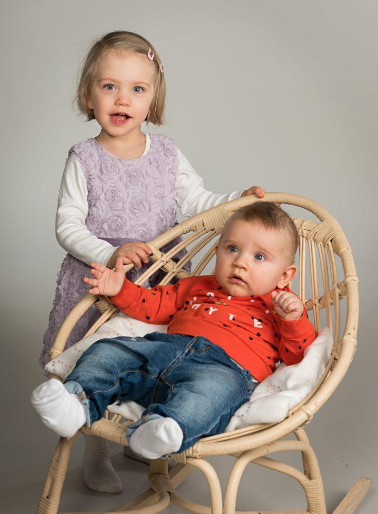 Sisaruskuva, poika keinussa ja tyttö seisoo takana.