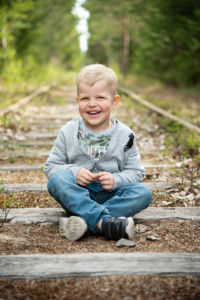 Lapsi istuu vanhalla junaradalla.