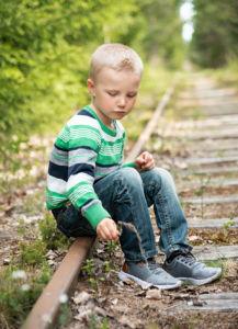 Poika istuu vanhalla junaradalla.